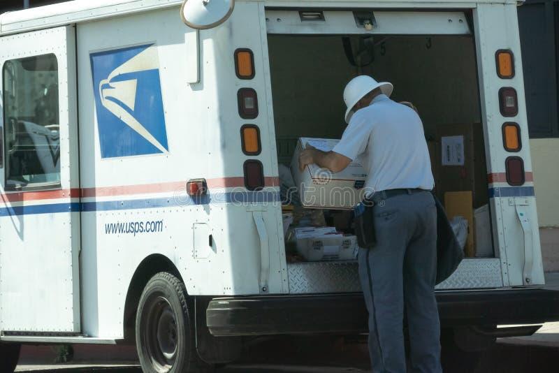 Почтовый работник на задней части тележки с пакетом стоковое изображение rf