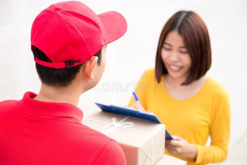 Почтовый работник доставляющий покупки на дом поставляя коробки к женщине стоковое фото