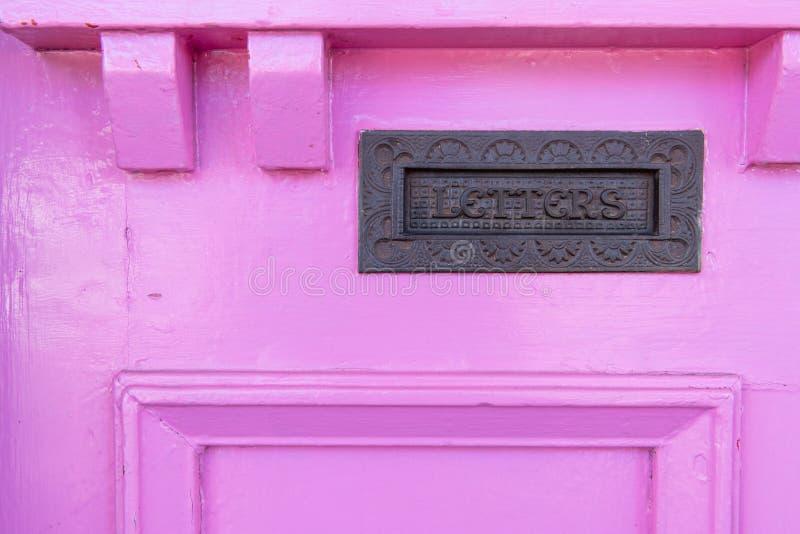 Почтовый ящик в грубо покрашенной деревенской розовой двери стоковое изображение rf