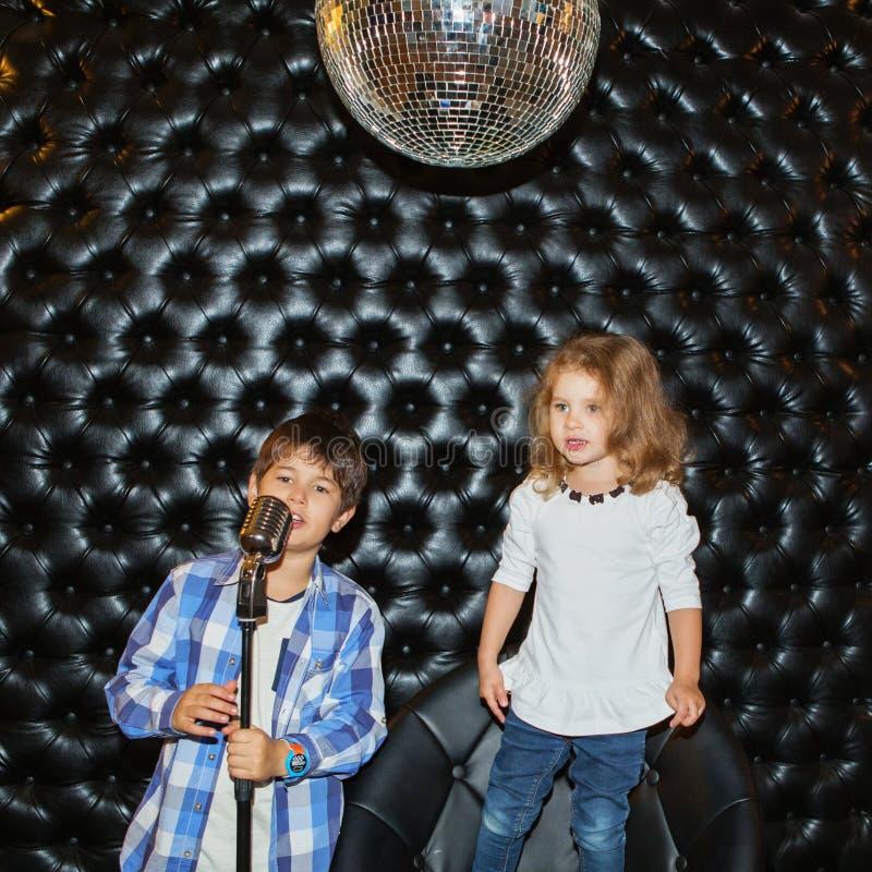 Поя маленькие дети с микрофоном на шкафе стоковое изображение rf