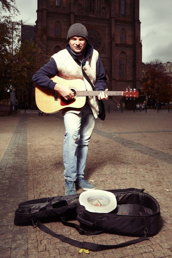 Поя попрошайка с гитарой перед церковью стоковое фото rf