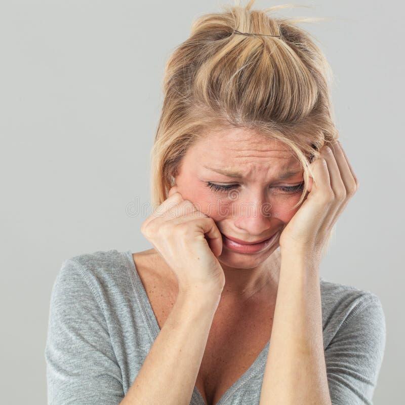 Подавленная женщина в боли выражая сожаление и тоскливость стоковые изображения rf