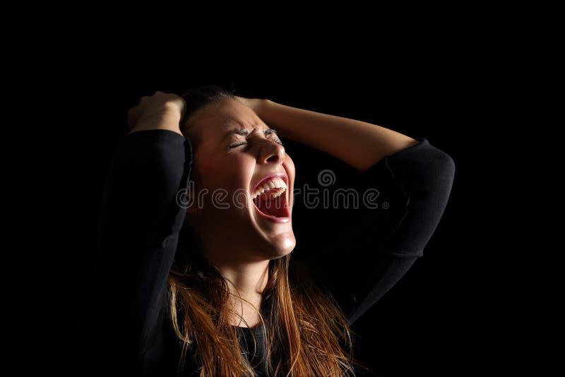 Подавленная женщина плача и крича отчаянная в черноте стоковое фото rf