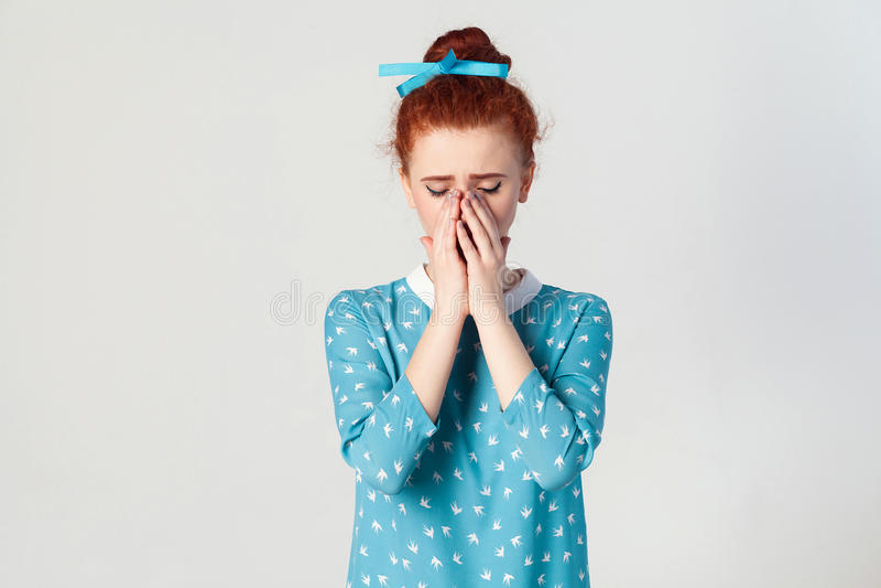 Подавленная и плача молодая кавказская девушка при волосы имбиря чувствуя пристыженный или больной, покрывающ сторону с обеими ру стоковые фото