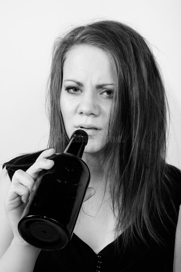 Подавленная молодая женщина выпивая от бутылки вина стоковые изображения