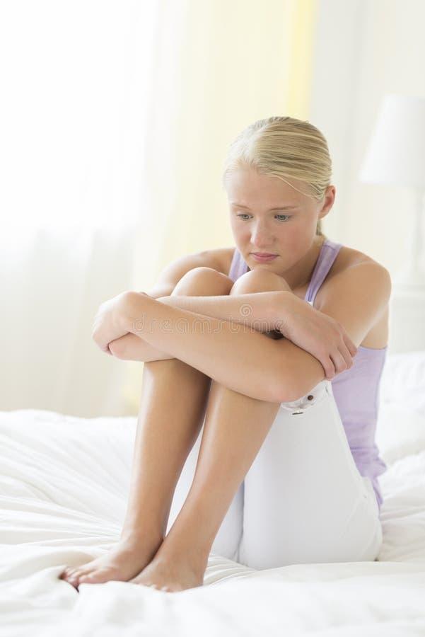 Подавленный девочка-подросток обнимая колени на кровати стоковая фотография rf