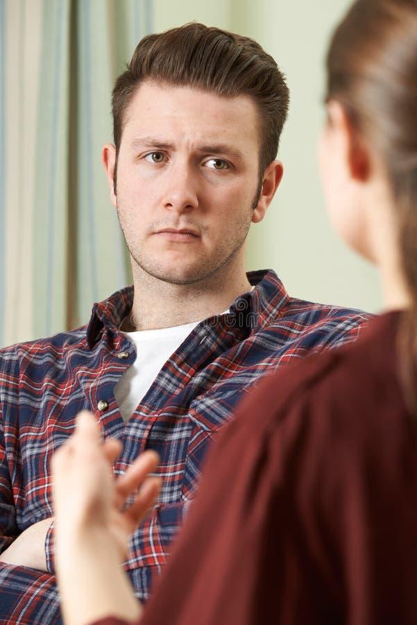Подавленный молодой человек говоря к консультанту стоковое изображение