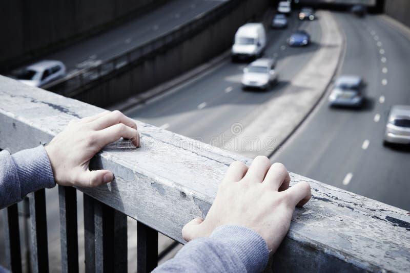 Подавленный молодой человек предусматривая суицид на мосте дороги стоковая фотография