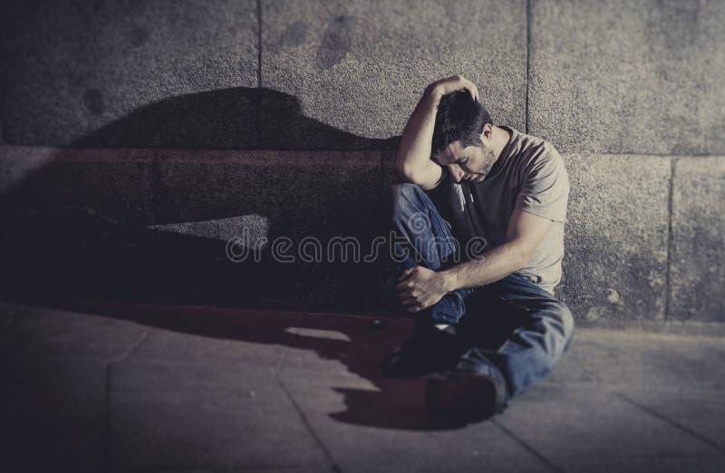 Подавленный молодой человек сидя на улице смолол с тенью на бетонной стене стоковые изображения rf