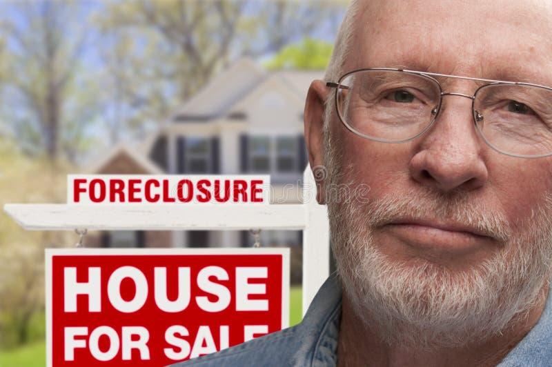 Подавленный старший человек перед знаком и домом лишения права выкупа стоковая фотография rf