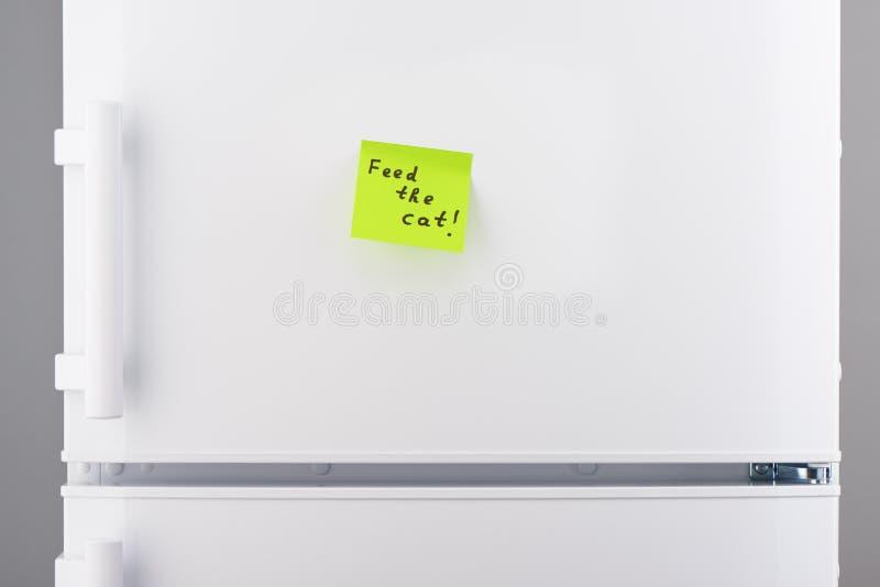 Подайте примечание кота на зеленой липкой бумаге на холодильнике стоковое фото rf