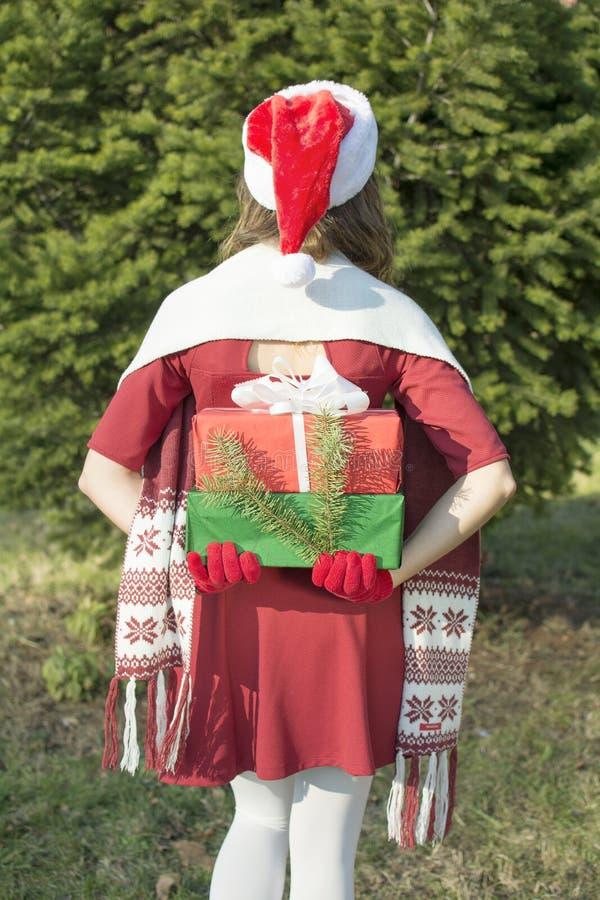 Подарки на рождество девушки Санта Клауса hidding стоковые фото