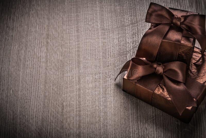 Подарки положенные в коробку - в glittery бумаге с коричневым жуликом торжества лент стоковые изображения rf