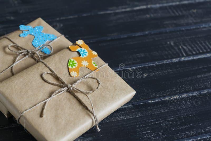 Подарки рождества в бумаге kraft с домодельной биркой на темной деревянной поверхности стоковые изображения rf