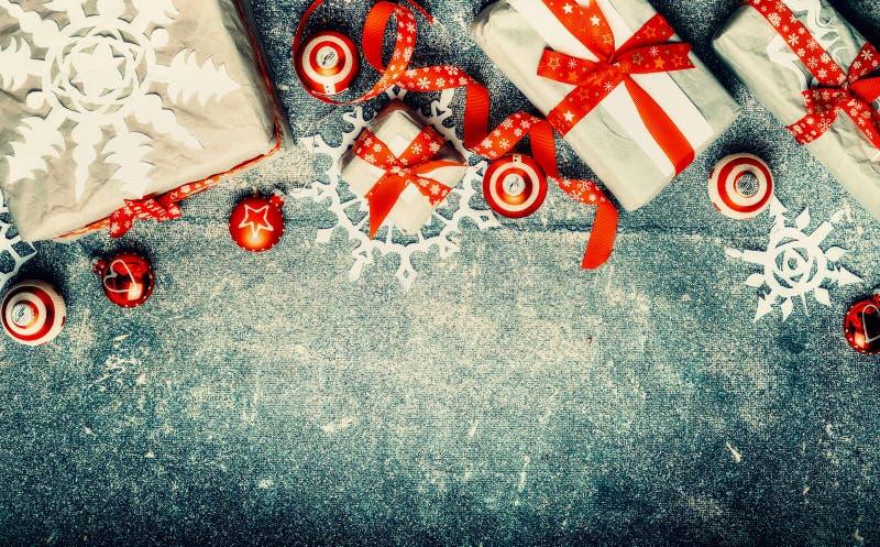 Подарки рождества, красные праздничные украшения праздника и бумажные снежинки на винтажной предпосылке, взгляд сверху стоковые изображения