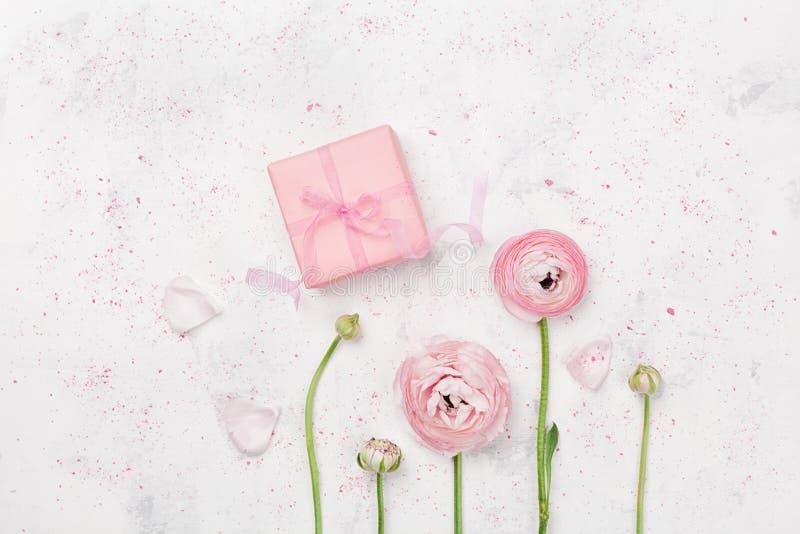 Подарок или присутствующий лютик коробки и красивых цветут на белой таблице сверху для wedding модель-макета или положения кварти стоковое изображение rf