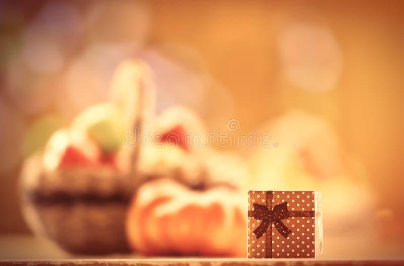 Подарок и тыква около корзины стоковое изображение rf