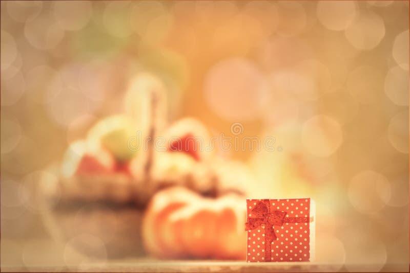 Подарок и тыква около корзины стоковые фото