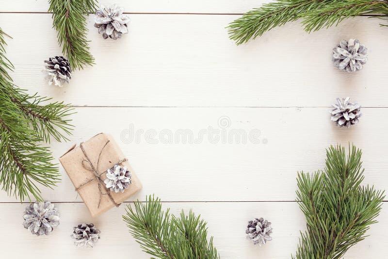 Download Подарок рождества, конусы сосны и ветви на белом деревянном столе S Стоковое Изображение - изображение насчитывающей рождество, конус: 81810601