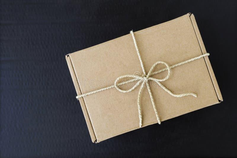 Подарочная коробка Брайна с естественной материальной строкой на черной предпосылке стоковые изображения