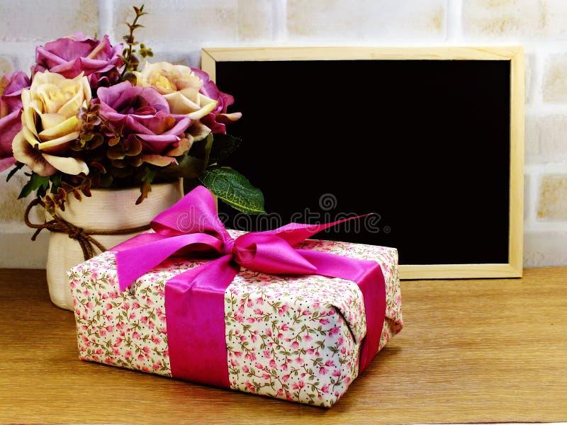 Подарочная коробка и ваза и космос цветков предпосылка стоковое фото rf