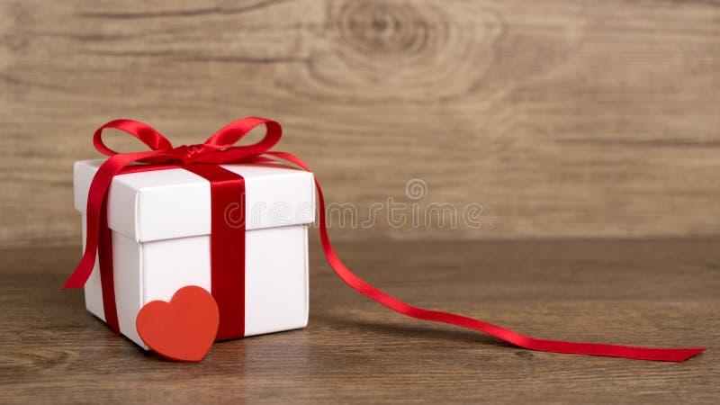Подарочная коробка на деревянной предпосылке красная тесемка красный цвет поднял стоковые изображения rf