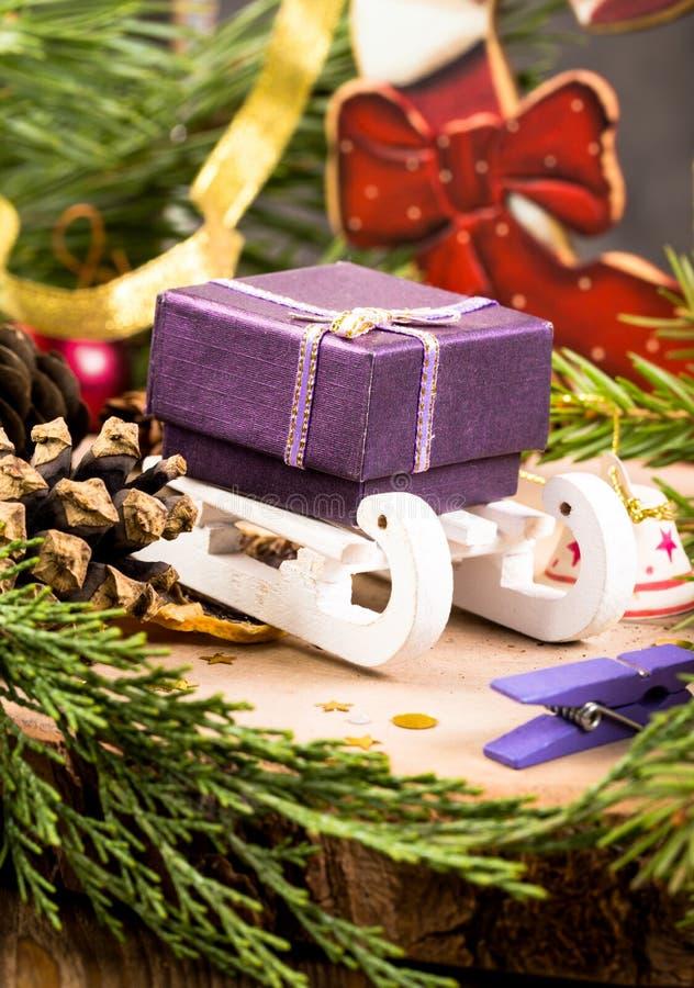 Подарочная коробка на розвальнях среди украшений рождества стоковое фото rf