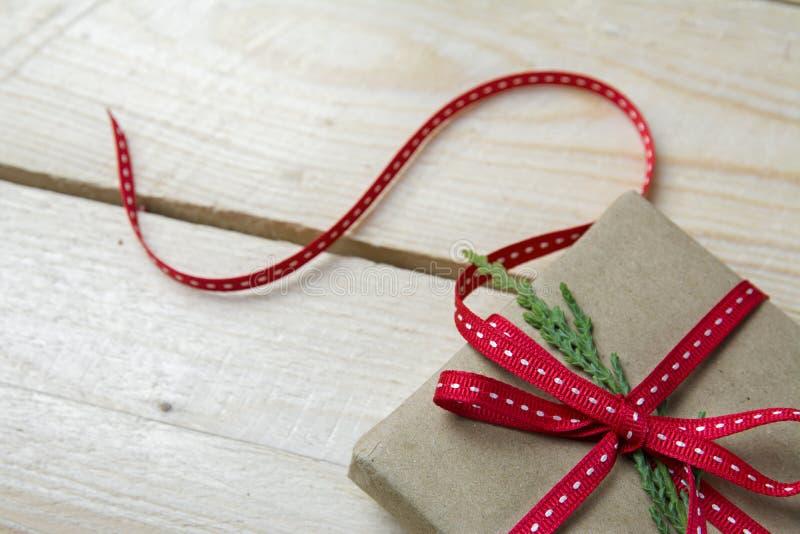 Подарочная коробка, обернутая в рециркулированной бумаге и красном смычке на деревянном backgrou стоковое фото rf