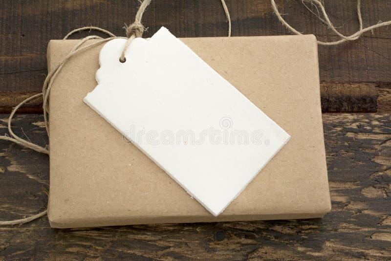 Подарочная коробка обернутая в рециркулированной бумаге с ярлыком стоковое изображение