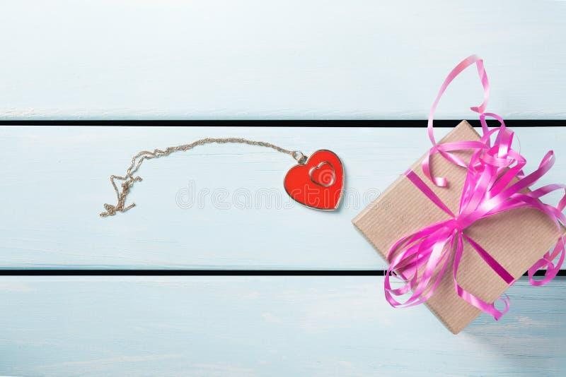 Подарочная коробка с славной розовой лентой и декоративное сердце с цепью на голубой деревянной предпосылке Открытый космос для т стоковое изображение rf
