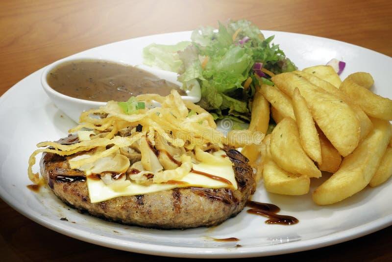 Подача стейка говядины с фраями и салатом француза стоковое фото