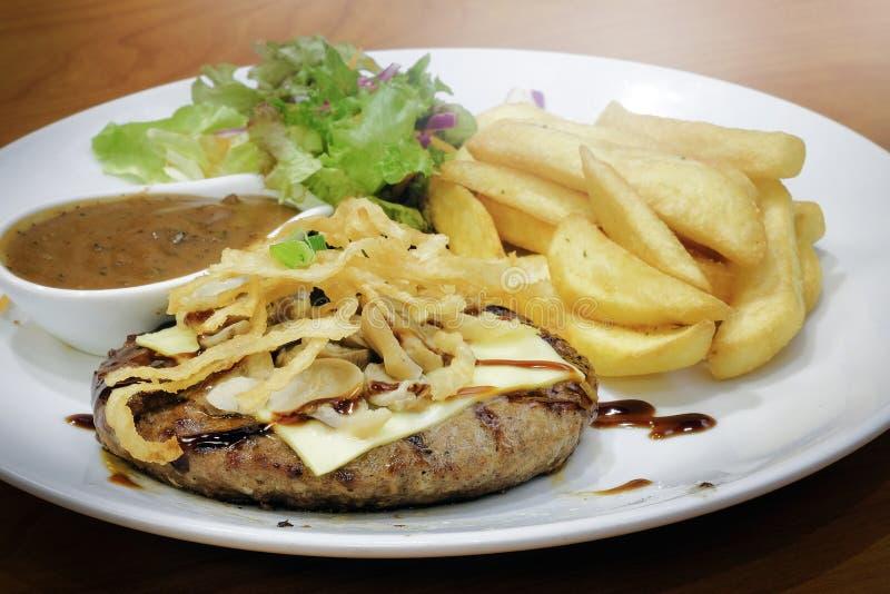 Подача стейка говядины с фраями и салатом француза стоковые изображения