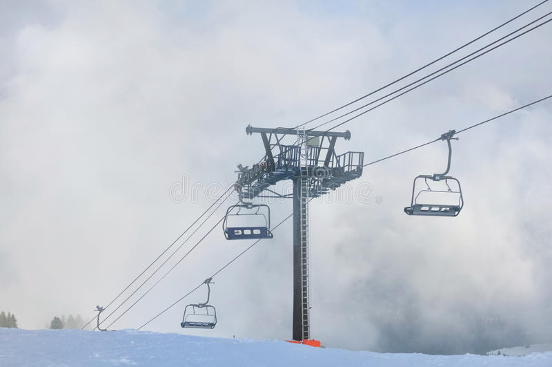 Подвесной подъемник в облаках в зиме стоковая фотография rf
