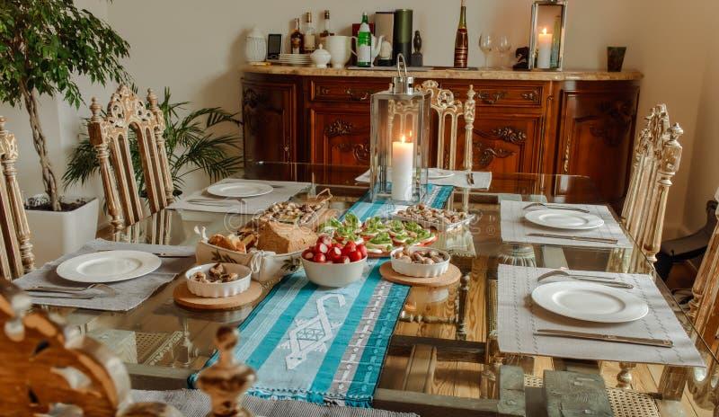 Подготавливайте для еды томатов с сыром, улитками и хлебом на таблице в красивом домашнем интерьере стоковое изображение