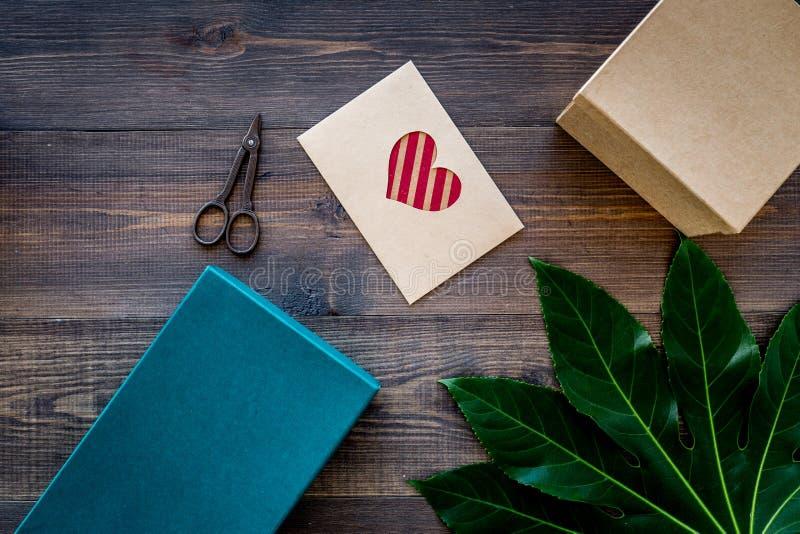 Подготавливать подарок и поздравительную открытку Подарочные коробки, карточка, конверт, copyspace взгляд сверху предпосылки лент стоковые изображения