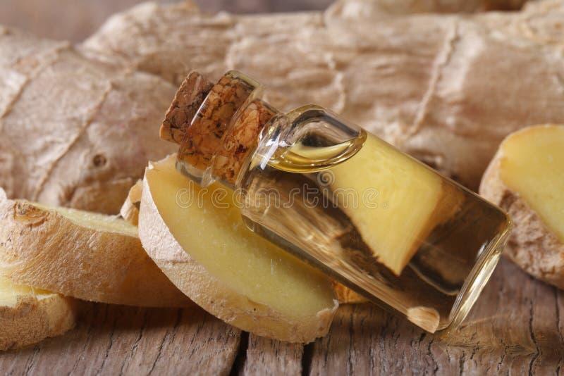 Полезное имбирное масло в макросе стеклянной бутылки горизонтальном стоковые фото
