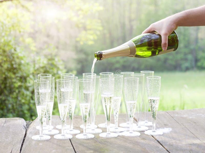 Полейте шампанское во время захода солнца стоковая фотография