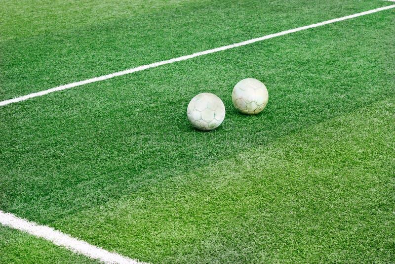 Поле зеленой травы с белой линией метки и старым футболом футбола 2 стоковое изображение