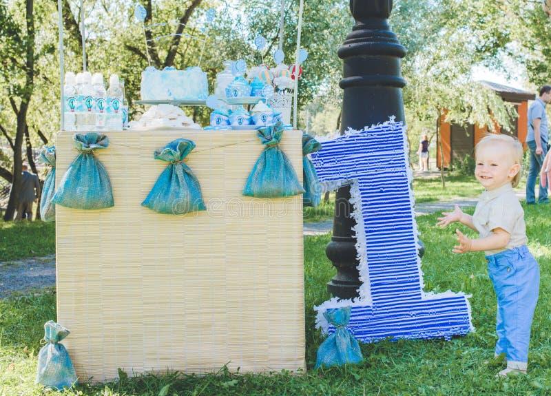 Поле травы, воздушный шар игрушки числового изображения одного близко большой, день рождения первого года жизни ребёнок усмехаясь стоковое изображение
