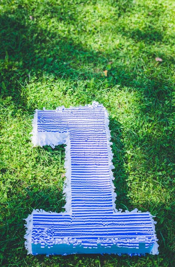 Поле травы, диаграммы лежа на траве, дня рождения первого года жизни стоковое изображение