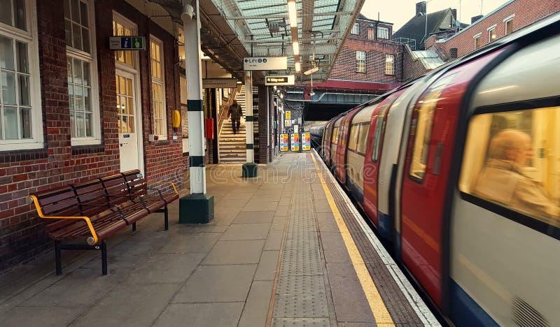 Подземная станция метро Kingsbury, поезд причаливая в городе Лондона, Великобритании стоковое фото
