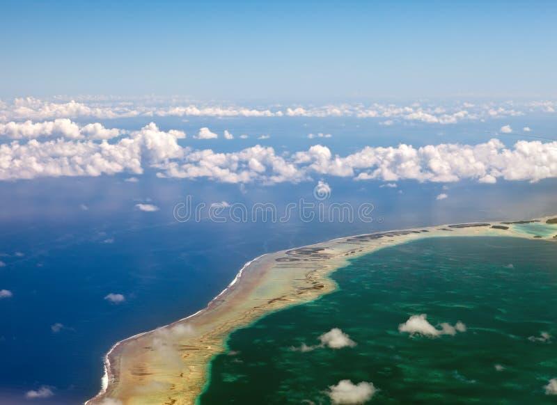 полинезия Атолл в океане через облака стоковая фотография rf