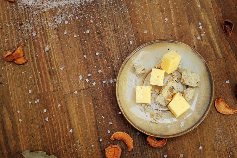 Подлинные кубы на плите, темная деревянная горизонтальная предпосылка сыра кухни стоковое фото