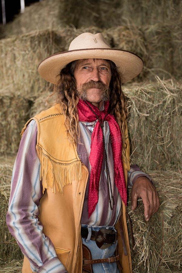 Подлинный западный ковбой с кожаным портретом жилета, ковбойской шляпы и шарфа стоковые изображения