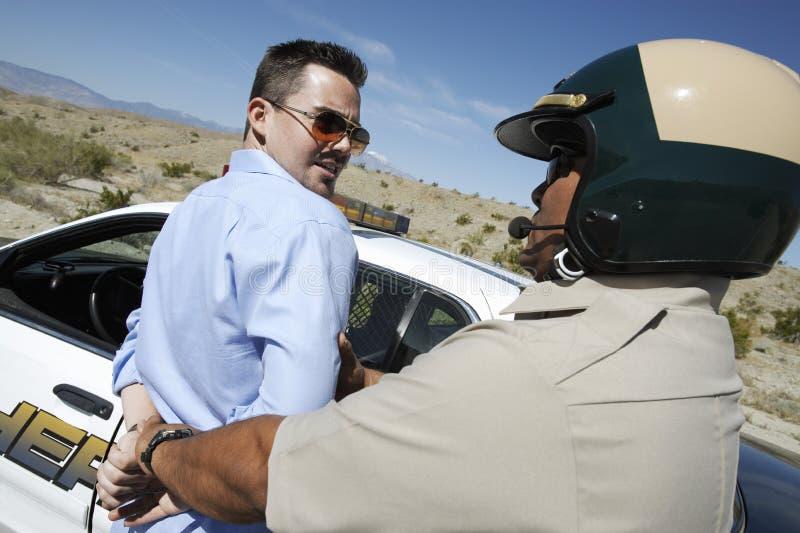 Полисмен арестовывая человека постаретого серединой стоковая фотография rf
