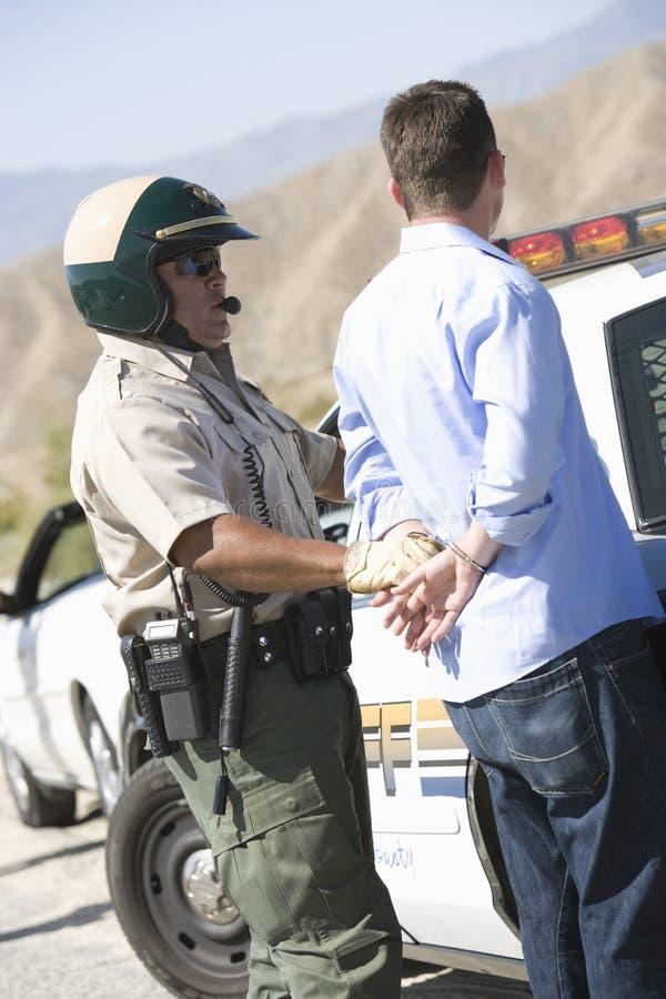 Полисмен арестовывая человека для ломать правила движения стоковые изображения