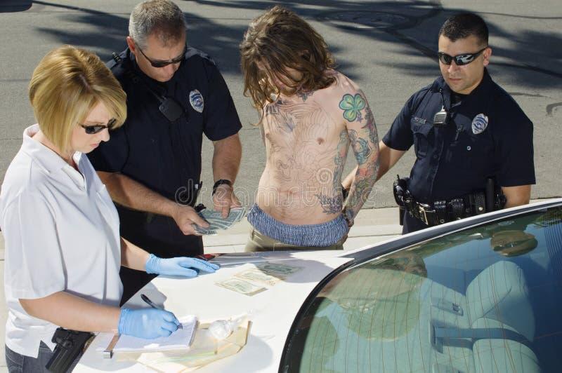 Полицейские арестовывая молодого человека стоковые изображения rf