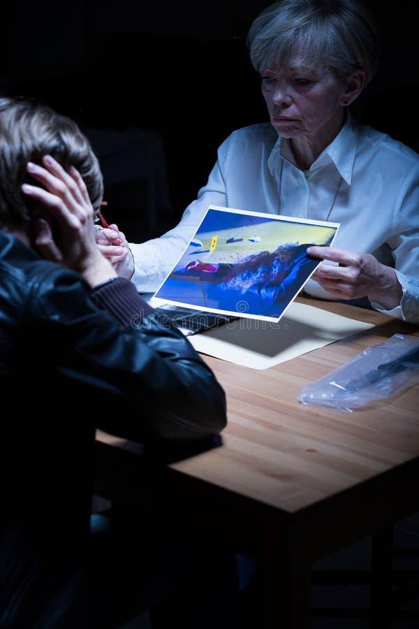 Полицейский агент показывая материалы от злодеяния стоковые изображения