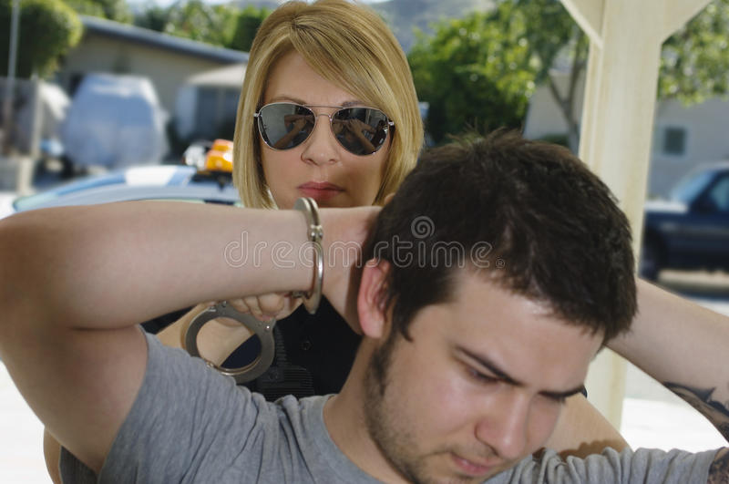 Полицейский арестовывая молодого человека стоковое фото