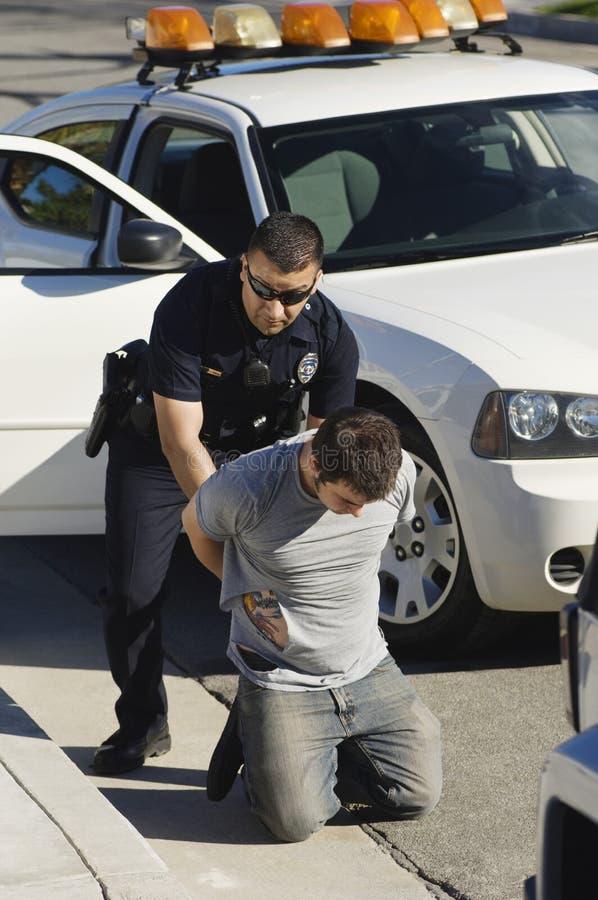 Полицейский арестовывая молодого человека стоковые фотографии rf